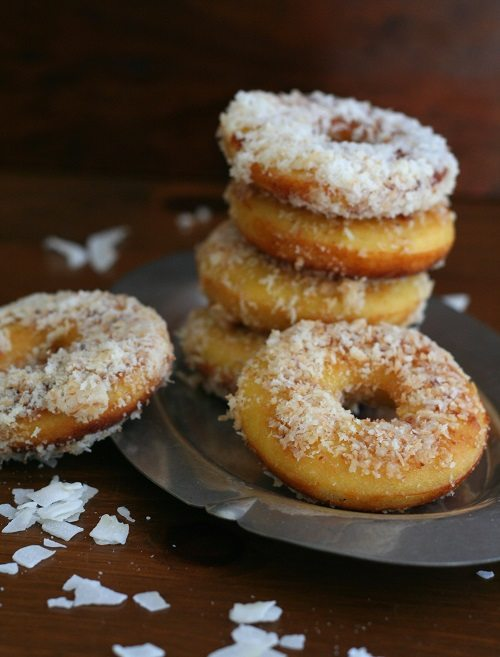 several low carb donuts topped with shredded coconut stacked on a plate