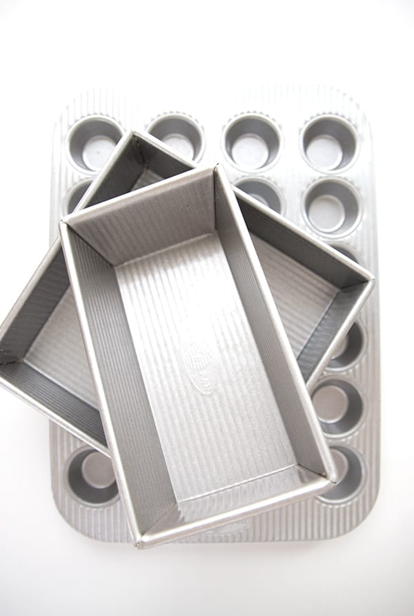Top down photo of good bakeware, including a loaf pan, square pan, and muffin pan.