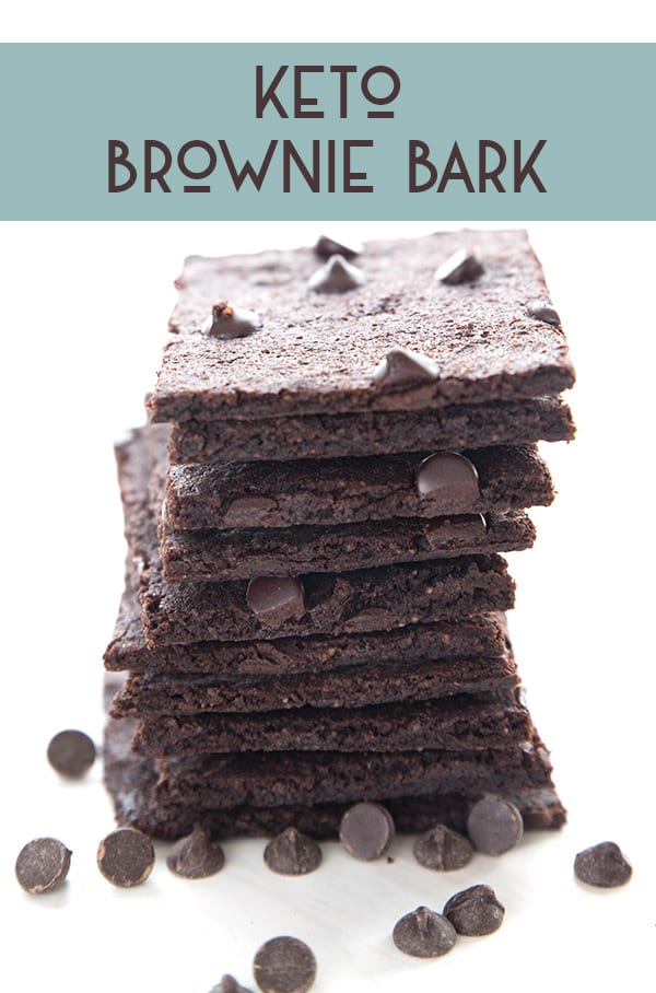 A stack of keto brownie crisps on a white background with sugar-free chocolate chips strewn around.