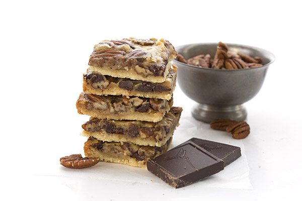 Grain Free Chocolate Pecan Pie Bars stacked next to a silver bowl filled with whole pecans