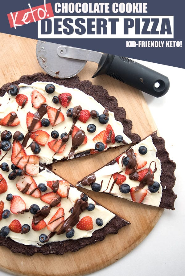 Top down image of keto cookie pizza on a pizza board with a slice cut out.