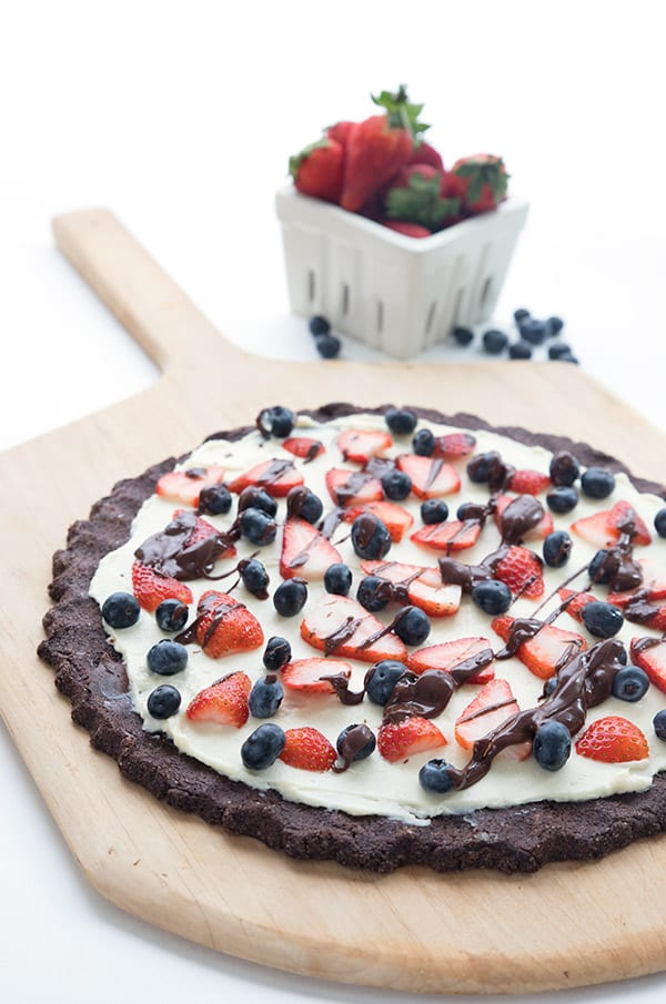 Keto Dessert Pizza on a cutting board with a basket of berries behind