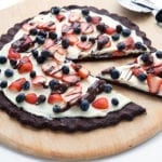 Chocolate Cookie Pizza with a slice cut out and a pizza wheel