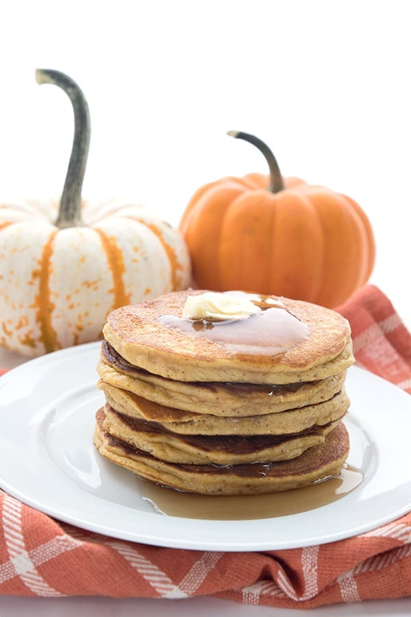 A stack of keto pumpkin pancakes on an orange napkin with pumpkins in the background