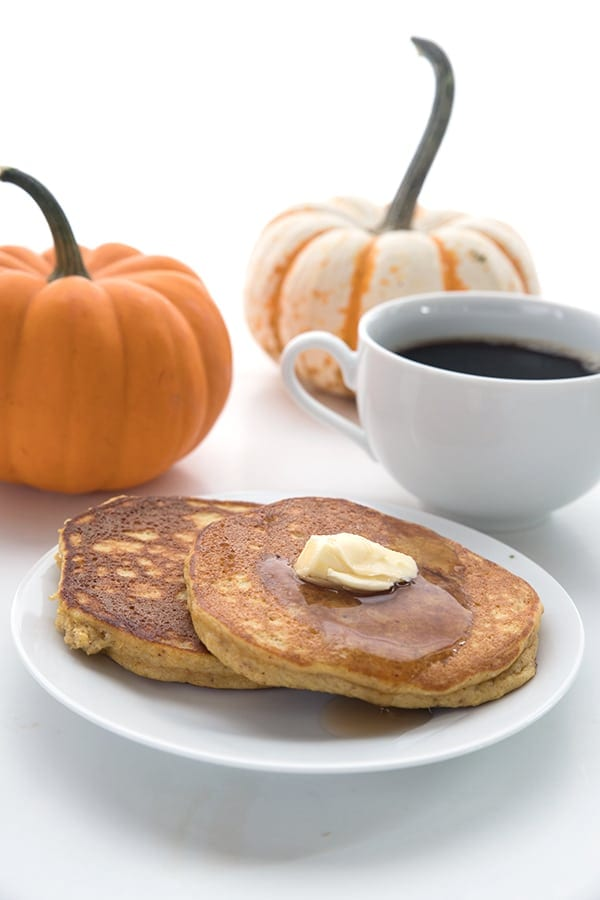 Two low carb pumpkin pancakes on a white plate with a cup of coffee
