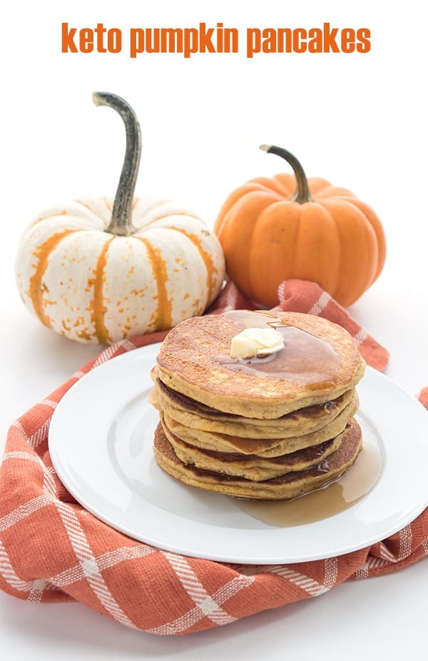 Easy keto pumpkin pancakes on a white plate with pumpkins in the background.