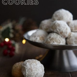 Titled image of keto snowball cookies on a metal cake stand with holiday lights in the background.