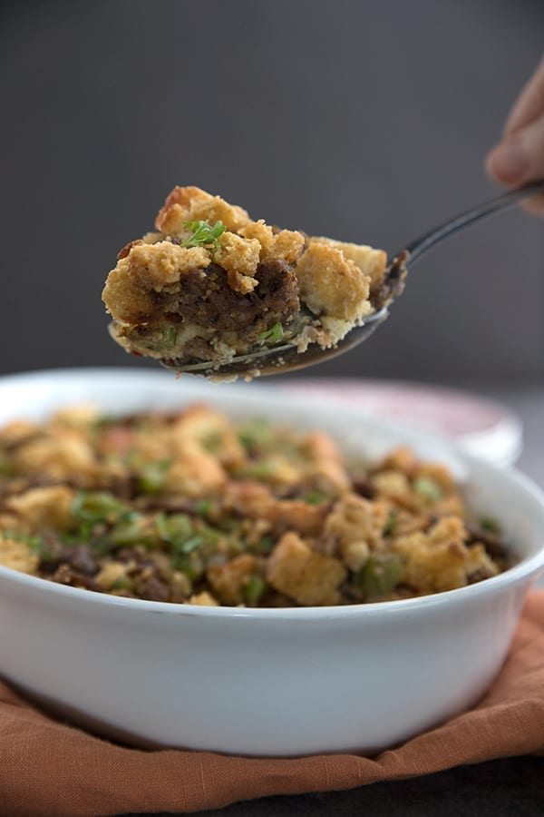 A big scoop of Keto Thanksgiving Stuffing on a spoon above the dish