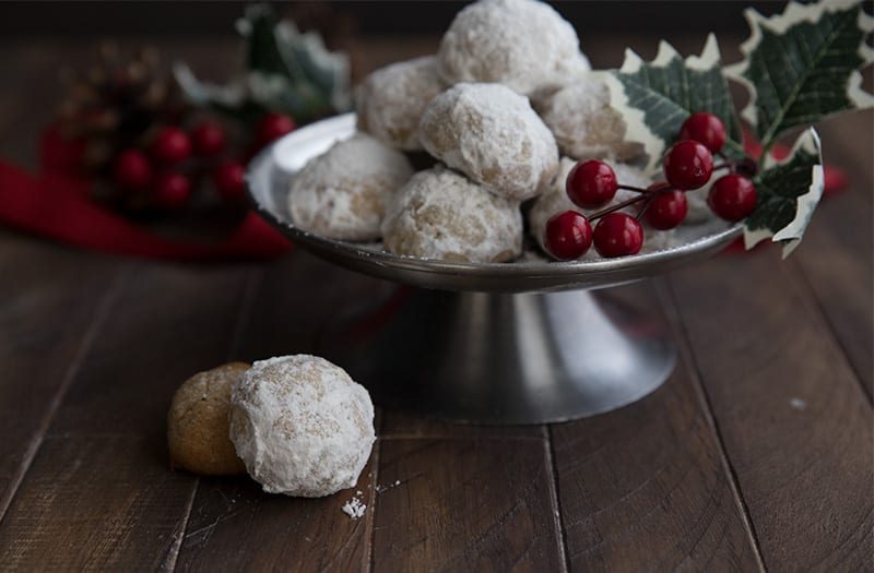 Ket snowballs on a metal cake stand with holly on the side.