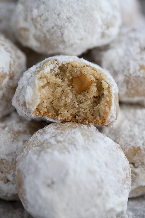 Close up of keto snowball cookies, one with a bite taken out of it.