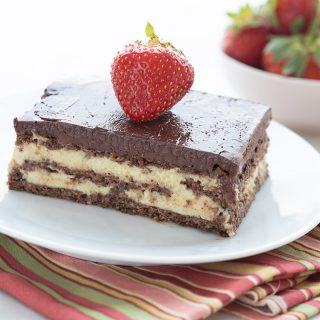 A slice of low carb eclair cake on a white plate with a strawberry on top, and a bowl of strawberries in the background.