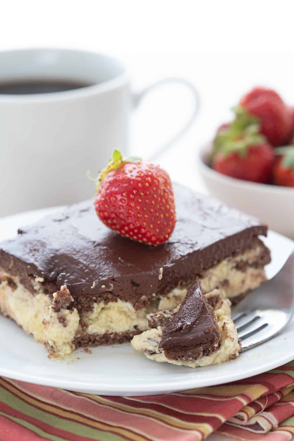 A close up shot of keto eclair cake with a forkful taken out of it. A cup of coffee and a bowl of strawberries in the background.