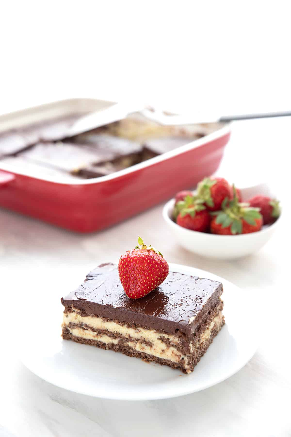 A slice of eclair cake on a white plate, in front of the pan with the rest of the cake.