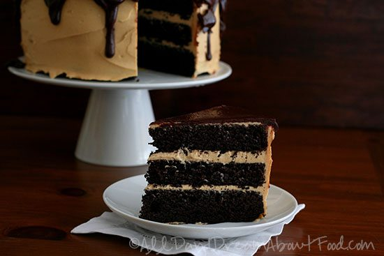 sugar free chocolate layer cake with peanut butter frosting on a cake stand, and a slice of the cake on a plate in the foreground