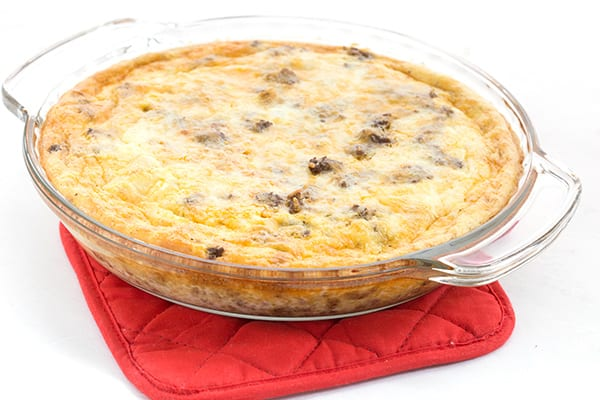 Easy taco pie in a pie plate on a red oven mitt