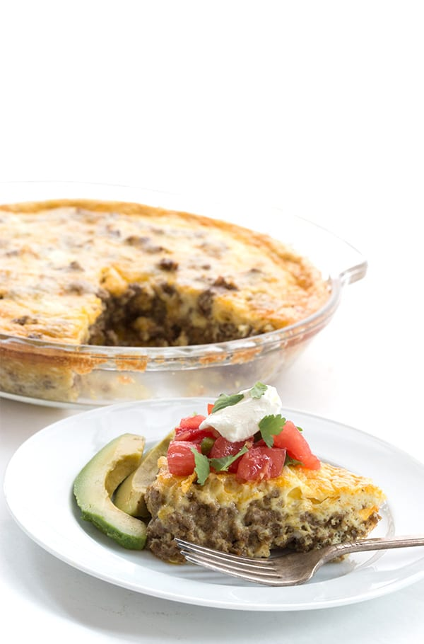 Easy keto taco pie on a white plate with the whole pie in behind.