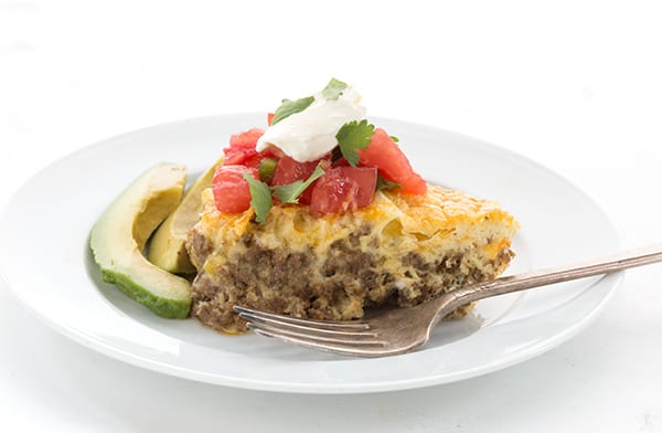 A slice of low carb taco pie on a plate with avocado, salsa, and sour cream