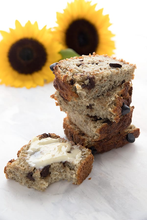 A stack of slices of keto banana bread in front of two sunflowers
