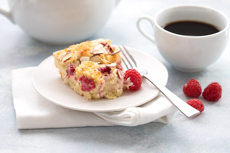 A slice of cream cheese coffee cake on a plate with raspberries