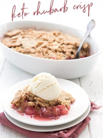 A serving of keto rhubarb crisp with ice cream on top in front of an oval dish with the rest of the crisp.