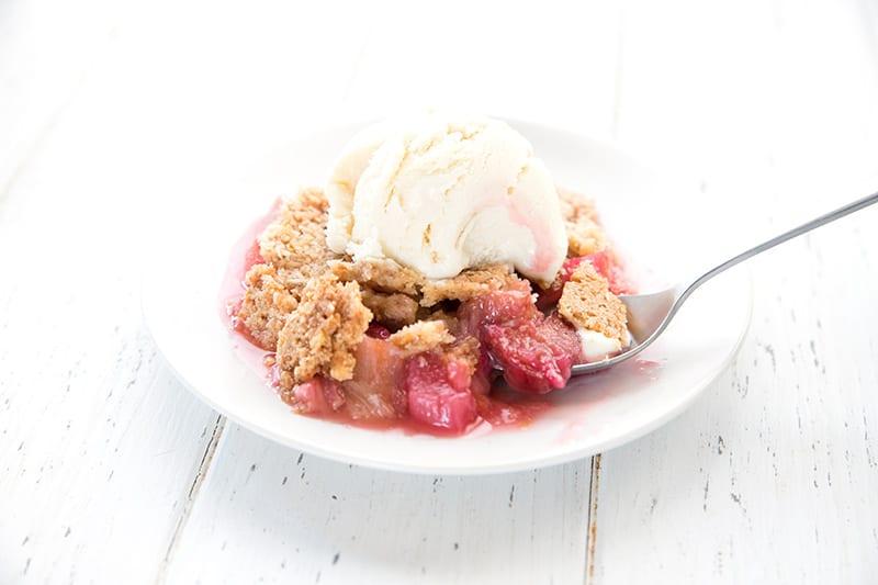 Rhubarb crisp with ice cream melting on top.