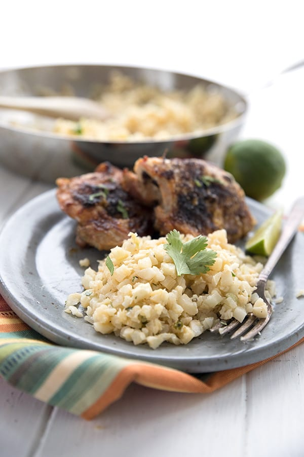Easy low carb Cilantro lime cauliflower rice on a plate with chicken