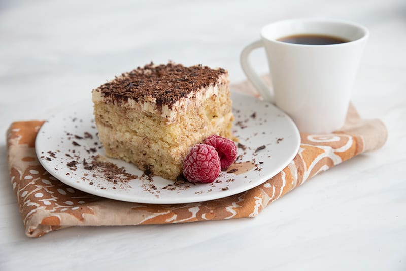 A piece of keto tiramisu on a white plate with raspberries and a cup of coffee.