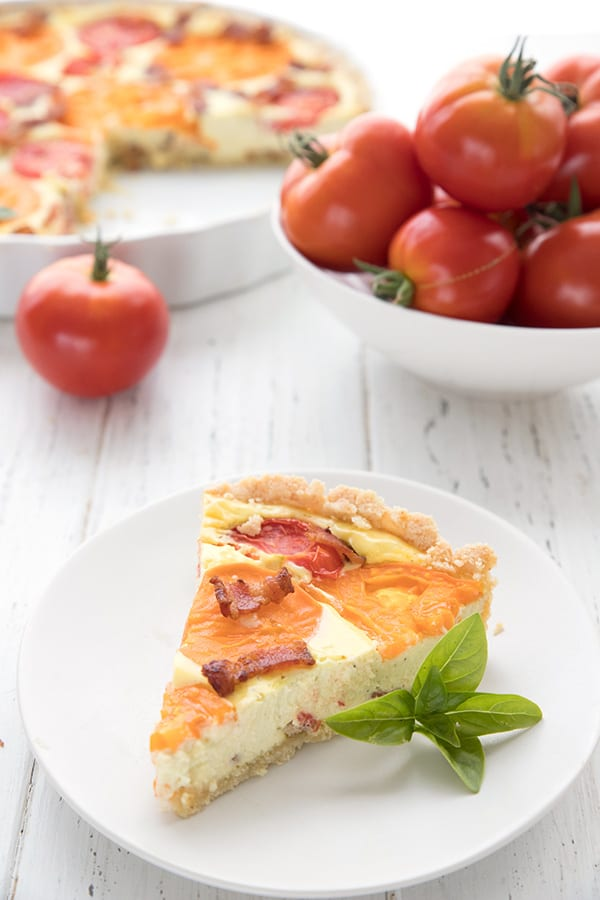 A slice of tomato goat cheese tart on a white plate with a bowl of tomatoes in the background.