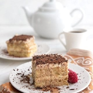 Titled image of keto tiramisu on white plates over a patterned napkin, with a white coffee cup and coffee pot in the background.