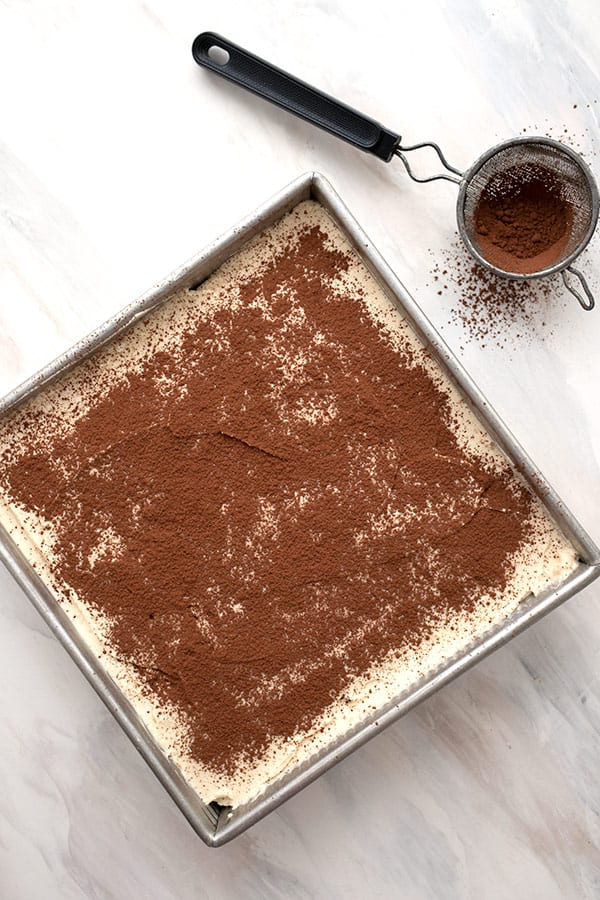 Top down image of easy keto tiramisu in the pan, with cocoa powder in a sifter.