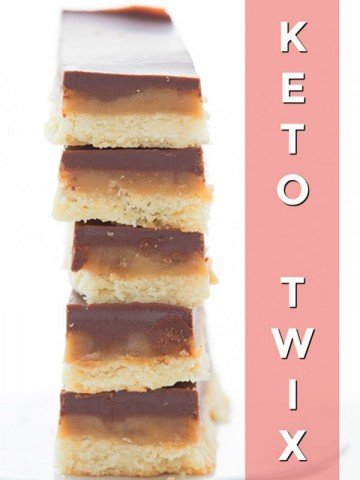 Titled image of a stack of keto Twix bars, close up to show the layers of caramel, chocolate, and shortbread.