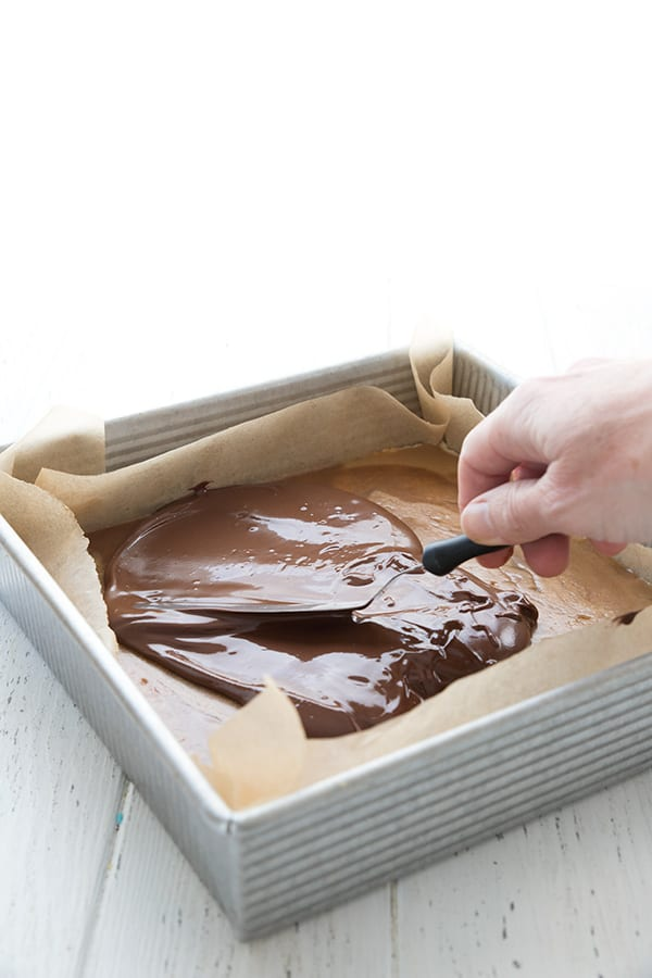 Spreading melted milk chocolate over homemade keto twix bars still in the metal pan.