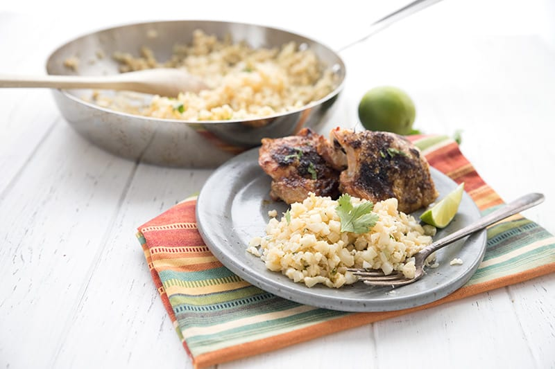 Cauliflower rice with cilantro and lime, on a plate with grilled chicken.