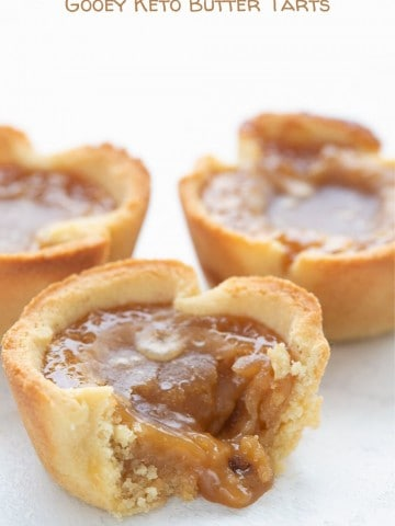 Titled image of a close up of keto butter tarts, with the front one broken open to show the gooey filling.