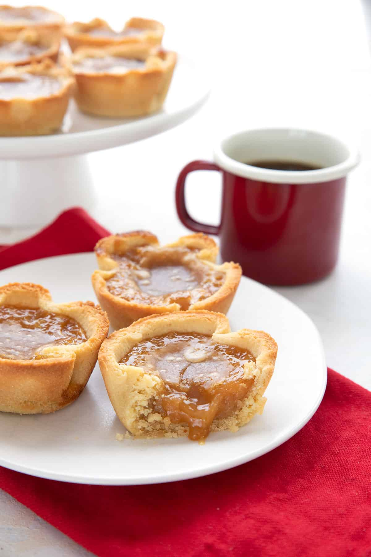 Three keto butter tarts on a plate over a red napkin with a cup of coffee in the background.