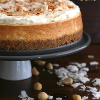 Keto Coconut Cheesecake on a cake stand with nuts and coconut around it.