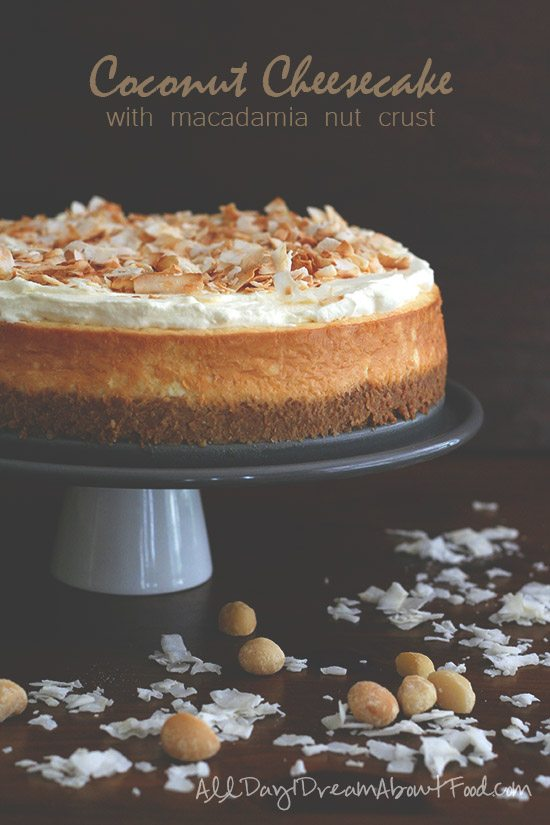 Titled image - Coconut cheesecake on a cake stand topped with macadamia nuts and flaked coconut.