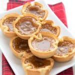 A white tray filled with keto butter tarts over a red plaid napkin
