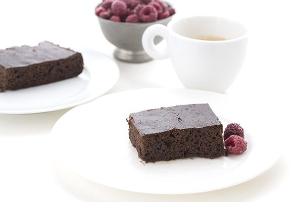 slices of gluten free low carb chocolate cake on white dessert plates, garnished with fresh raspberries