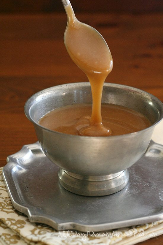 low carb caramel sauce sliding off of a spoon into a big silver bowl full of the sauce