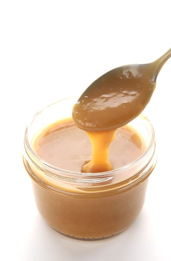 Gooey low carb caramel sauce pouring off a spoon back into the jar