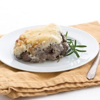 A piece of cauliflower shepherd's pie on a white plate with a sprig of rosemary