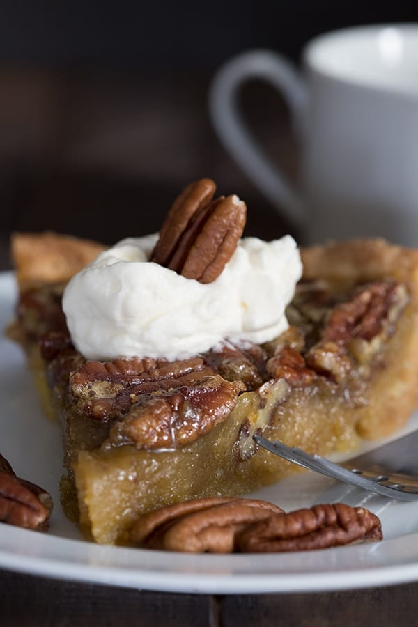 Close up of a slice of sugar free pecan pie on a white plate with a fork