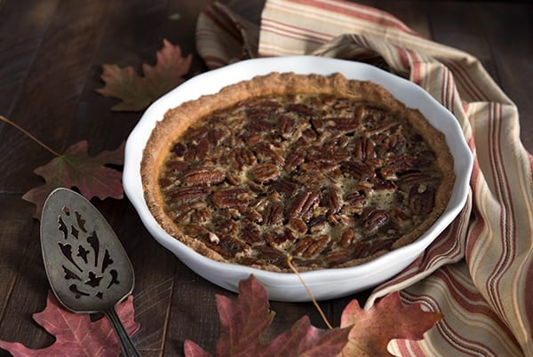 Low carb pecan pie in a white pie dish on a brown background with maple leaves around it.