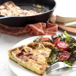 Keto Bacon Frittata on a white plate with a cast iron skillet in the background