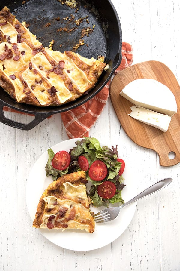 Top down photo of bacon and brie frittata on a white table.