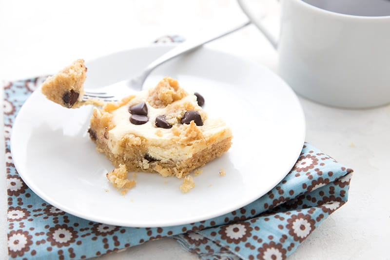 A white plate with a keto chocolate chip cookie cheesecake bar on it over a blue patterned napkin.