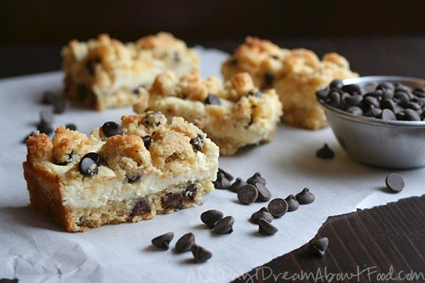 keto Chocolate Chip Cheesecake Bars with almond flour cheesecake crust sitting on parchment paper, surrounded by sugar free chocolate chips
