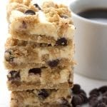 A stack of chocolate chip cheesecake bars with a cup of coffee in behind.
