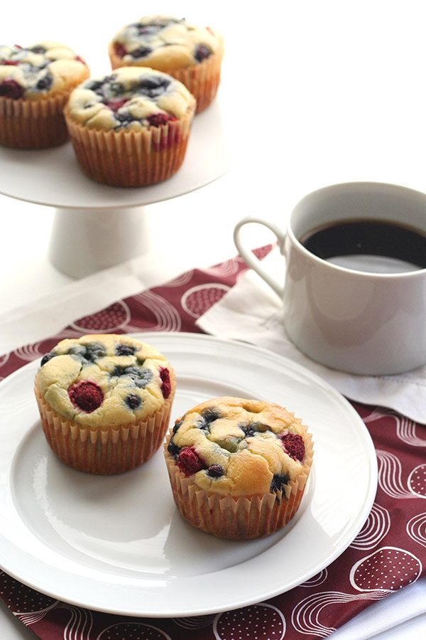 two grain-free and sugar-free pancake muffins stuffed with fresh berries, sitting on a plate next to a mug of coffee